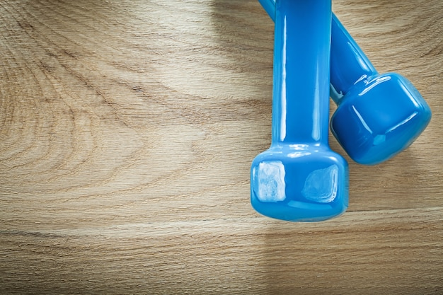 木の板のフィットネスの概念に青いダンベルのペア