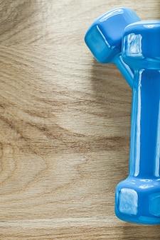 木の板に青いダンベルのペアスポーツトレーニングコンセプト