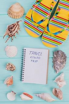 明るいフリップフロップのペアは貝殻に囲まれています。旅行とリラックスのコンセプト。作曲の中心にあるメモ帳に書かれた旅。