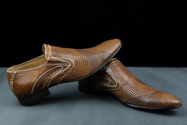 Пара коричневых туфель на черном фоне. модная мужская обувь. классическая мужская обувь из натуральной кожи. мужские аксессуары. элегантная стильная обувь