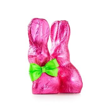 白い背景の上のピンクのホイルで包まれた弓とチョコレートイースターウサギの甘いバニーのペア