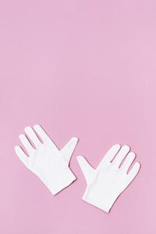 분홍색 옷 장갑의 쌍입니다. 미용 절차를 위해 흰색 패브릭 장갑.