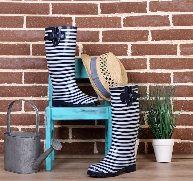 カラフルな長靴のペア、鉢植え、椅子、じょうろが色の表面にあります
