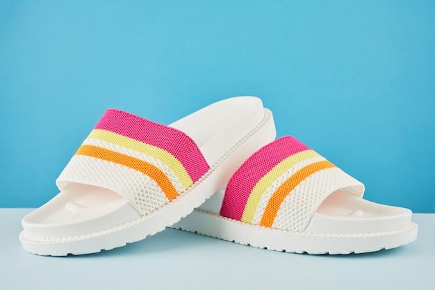 Пара красочных разноцветных шлепанцев радуги или сандалий на пастельной стене. пляжные каникулы и летняя концепция с копией пространства.