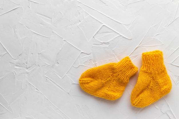 흰색 퍼티 질감 배경에 귀여운 오렌지 니트 아기 양말의 쌍. 출산.