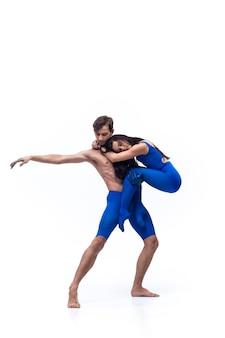 Пара танцоров в синей одежде танцует в студии