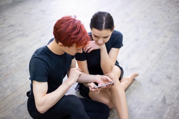 携帯電話で学びたい要素を見ながら床に座っているダンサーのペア