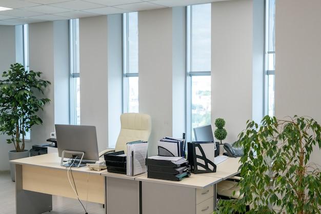 Пара столов с компьютерными мониторами и документами, стоящими вдоль окон
