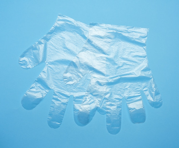 青色の背景に使い捨てのポリエチレン手袋のペア