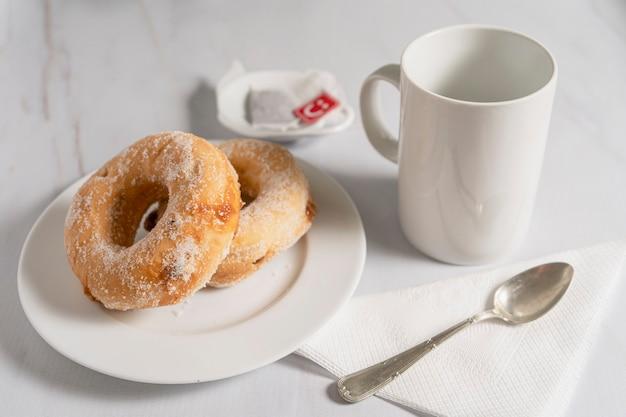 설탕을 넣은 도넛 한 쌍과 대리석 테이블에 흰색 컵이 있는 하얀 접시에 달콤한 것으로 채워져 있습니다. 아침 식사 개념입니다.