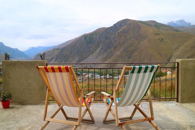 Пара пустых шезлонгов на веранде с прекрасным видом на горы