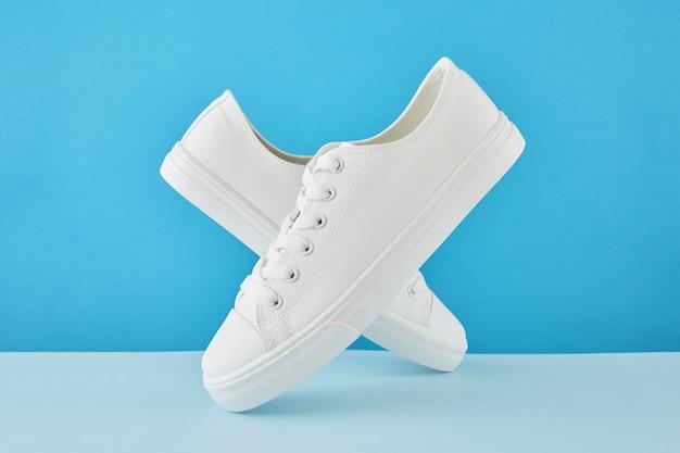 パステルブルーの背景にファッションスタイリッシュな白いスニーカー、ランニングスポーツシューズのペア。