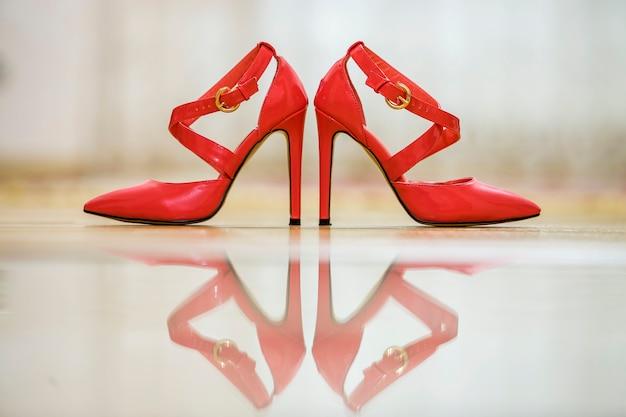 Пара модных туфель на высоком каблуке из кожи с вырезом красного цвета, с золотыми пряжками на светлом фоне.