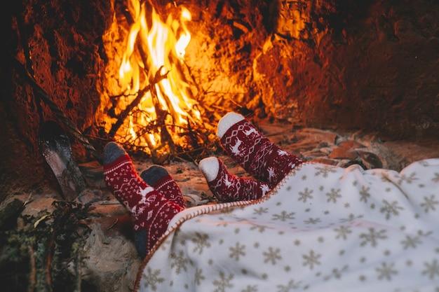 クリスマスの暖炉のそばのウールの靴下の足のペア。カップルは暖かい火でリラックスします。足でクローズアップ。冬とクリスマスの休日のコンセプト。愛とロマンスの人々の家