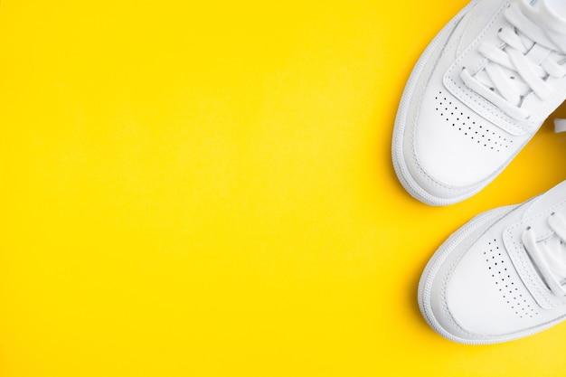 노란색 배경에 여성 세련된 흰색 캐주얼 운동화 한 켤레
