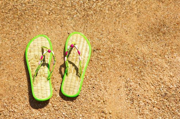 海辺の濡れた砂のビーチサンダルのペア