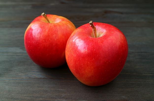 暗い色の木製の表面で分離された新鮮な熟した赤いリンゴのペア
