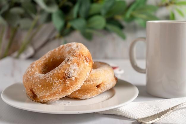 흰색 컵과 흰색 접시에 퍼지 채워진 도넛 한 쌍. 아침 식사 개념입니다.