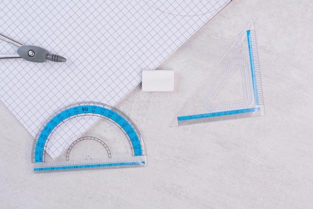 白いテーブルの上の幾何学コンパスと紙のペア。