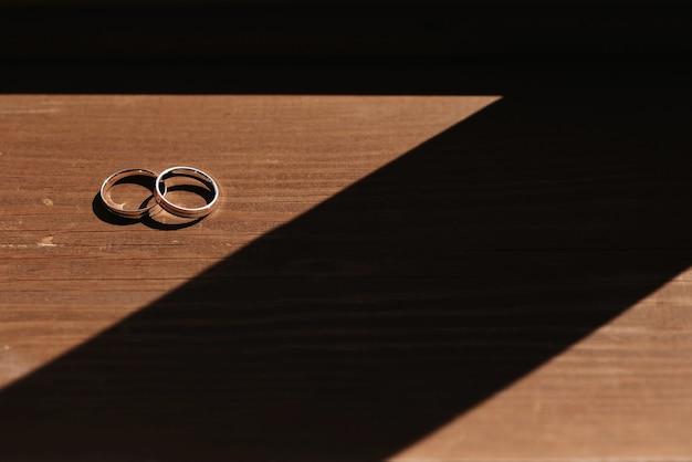 Пара золотых обручальных колец на деревянной поверхности крупным планом