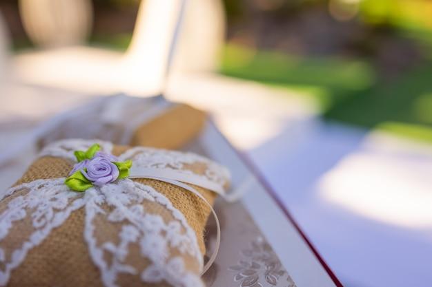 小さな白い布のクッションに金の指輪のペア。