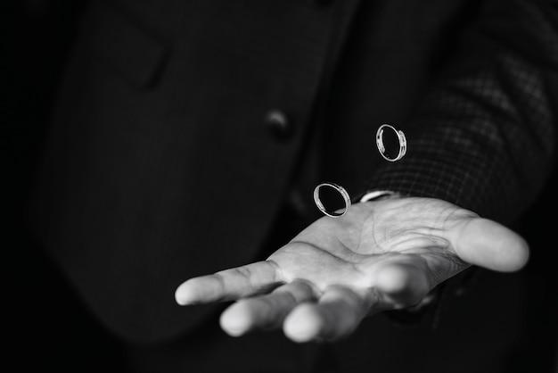 金の婚約指輪のペアは、スーツを着て新郎の手の上を飛ぶ