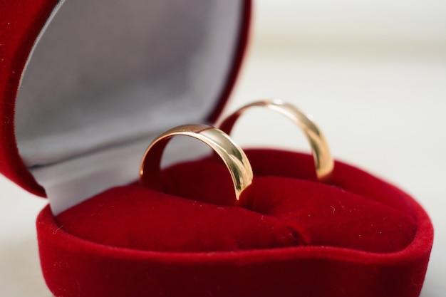 Пара золотых обручальных колец лежит в красной коробке крупным планом