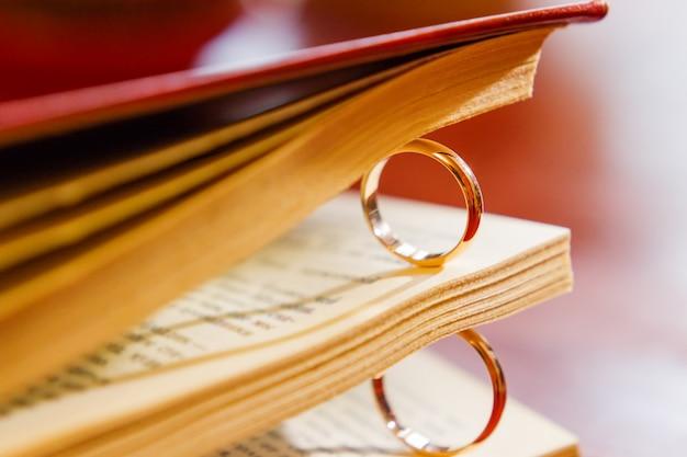 책 페이지 사이의 황금 결혼 반지 쌍