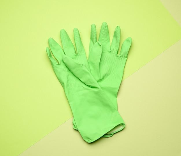 Пара зеленых защитных резиновых перчаток для чистки на зеленом, вид сверху
