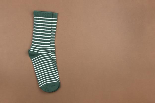 茶色の背景に緑の縞模様の靴下のペア、フラット、最小限のスタイル、上面図、コピースペース。コンセプトの男性服、ハウスキーピング、仕分け、整理、整理。水平フォーマット。