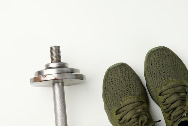 녹색 섬유 운동화 한 켤레와 흰색 배경에 금속 아령, 위쪽 전망. 스포츠용 신발