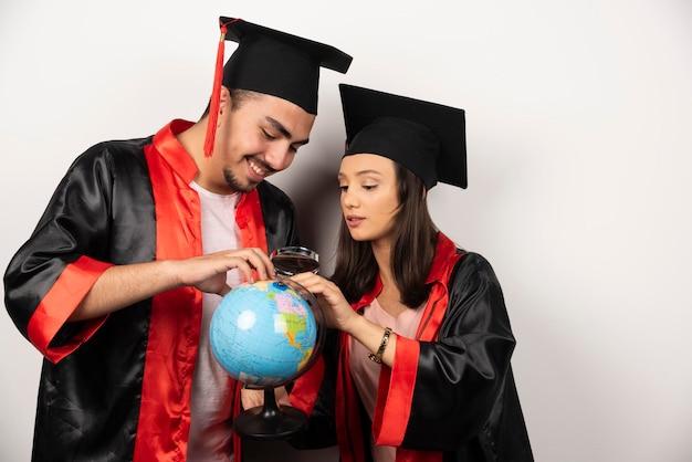 Пара счастливых студентов в халате, глядя на глобус на белом.