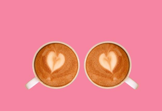 플라밍고 분홍색 배경에 고립 된 심장 모양의 라떼 아트 카푸치노 커피 한 켤레