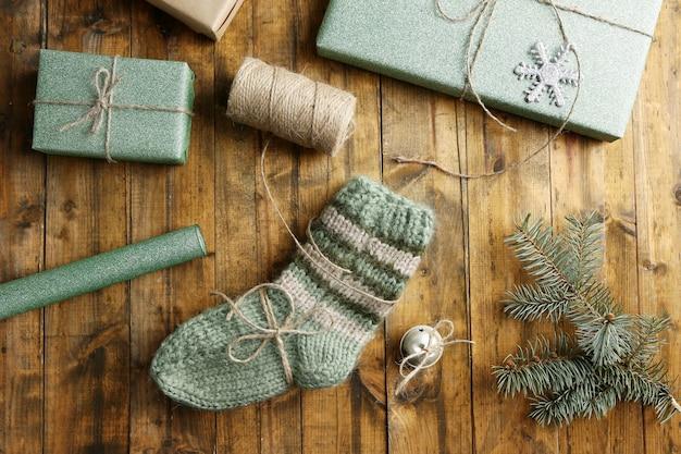 나무 테이블에 크리스마스 선물을 포장한 니트 양말 한 켤레