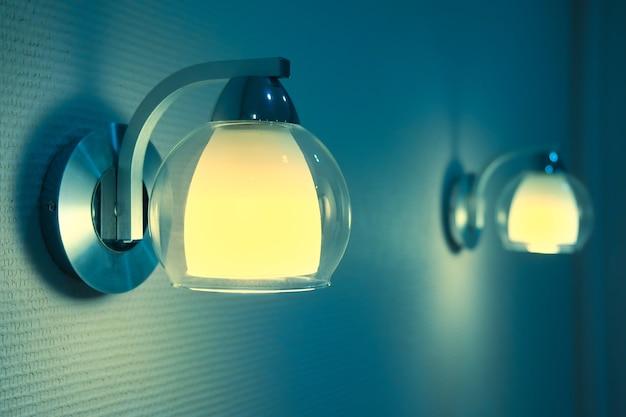 寝室のランプのペアが点灯します。 2つの常夜灯の青と黄色のトーン画像。