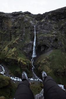 Пара ног с видом на водопад