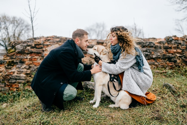 Пары любовников гуляя с осиплым щенком напольным в сельской местности весной. мужчина и женщина с их маленьким пушистым любимым домашним домашним животным обниматься и отдыхать на природе в пасмурный день.