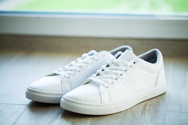 Пара новых стильных белых кроссовок на деревянный пол.