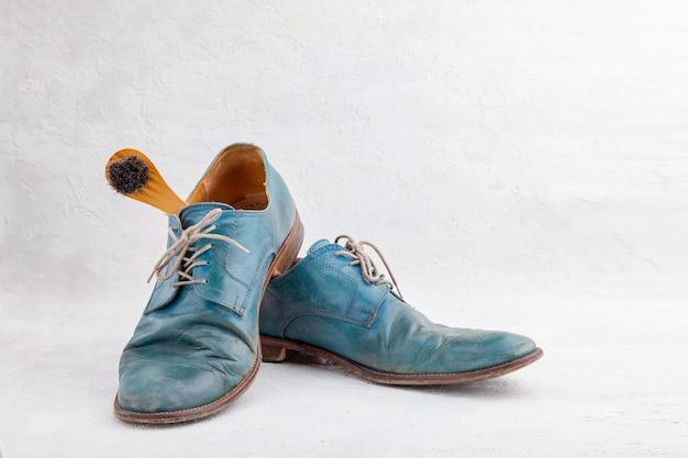 古い革の青いブーツと靴ひも付きの靴ブラシのペア