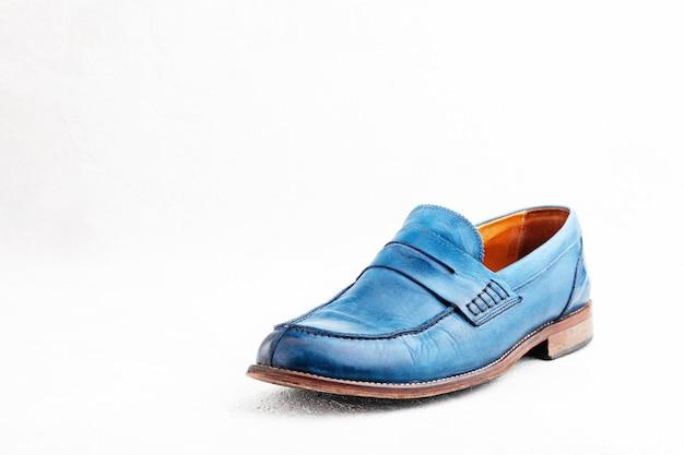 靴ひもが付いている古い革青い破棄されたブーツのペア