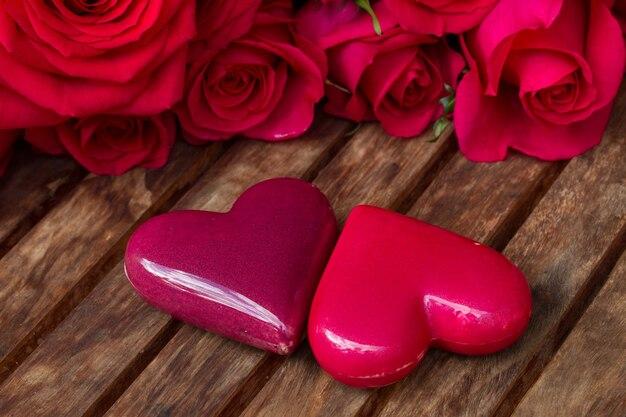 나무 테이블에 장미와 핑크 하트의 쌍