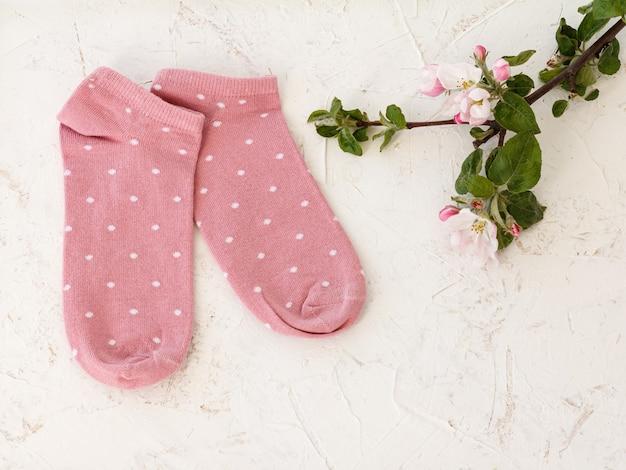 ピンクの女性の靴下と白い構造化された背景、上面図にリンゴの木の花のペア。