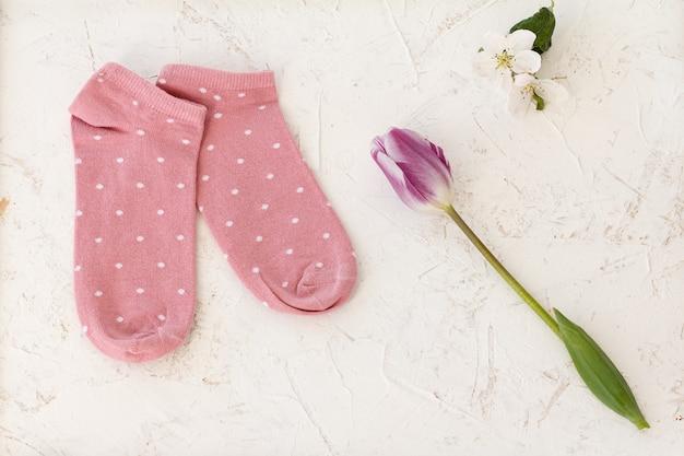 ピンクの女性の靴下、チューリップ、白い構造の背景にリンゴの木の花のペア、上面図。