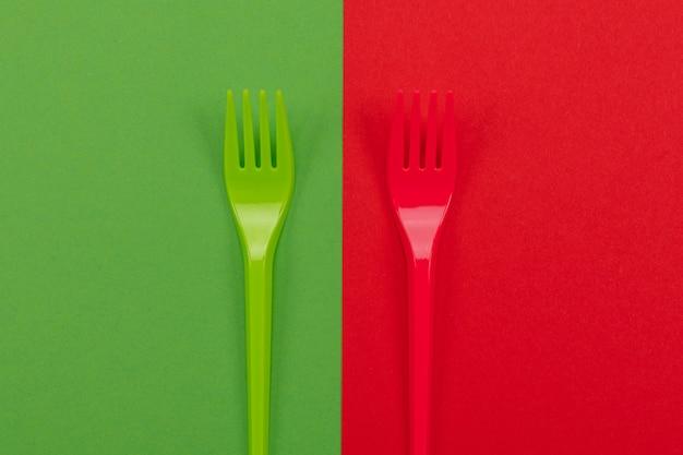 Пара пластиковых вилок в красном и зеленом поверх фона