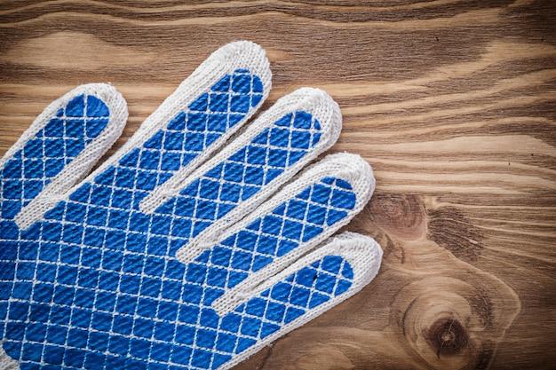 Пара защитных перчаток на деревянной доске
