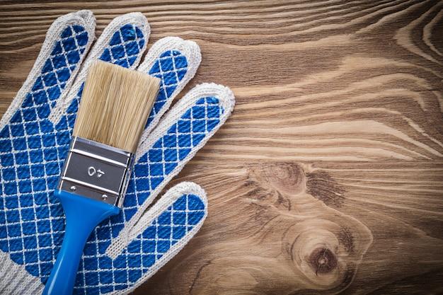 Пара защитных перчаток, кисть на деревянной доске