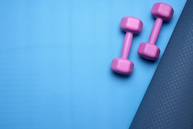 青いネオプレンマットの上の紫色のダンベルのペア