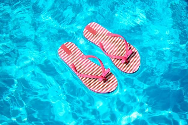 夏に輝く太陽に照らされたプールの青い水の上に浮かぶ赤と白のストライプのビーチサンダルのペア
