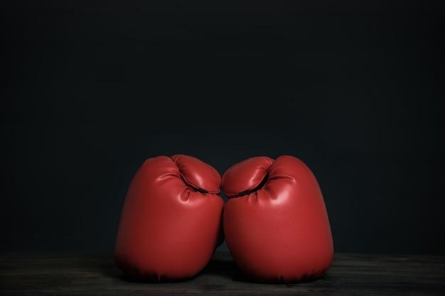黒の背景に赤いボクシンググローブのペア。コピースペース
