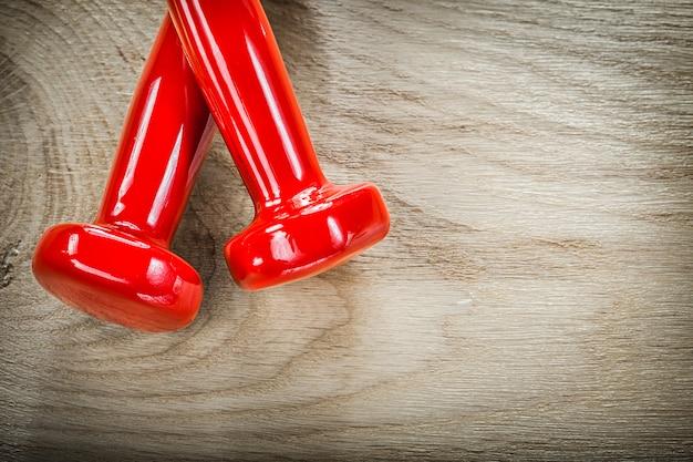 木板スポーツトレーニングコンセプトに赤いダンベルのペア
